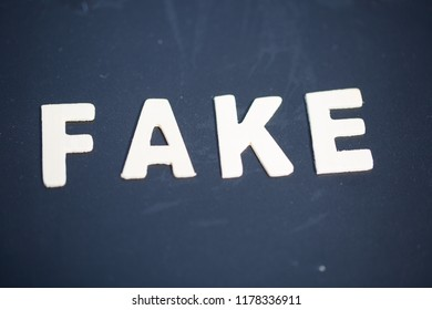 Fake, fact, as text, letters on wood, black background