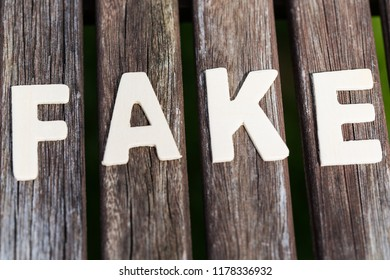 Fake, fact, as text, letters on wood