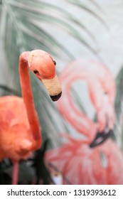 A fake flamingo next to a painted flamingo.