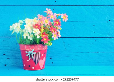 Fake flowers for interior decoration on blue paint wood background.