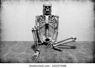 Fake human skeleton sitting against the wall with cigarette in his mouth.