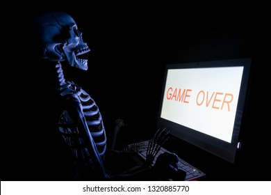 Fake human skeleton sitting in front of desktop computer, computer addicted concept.
