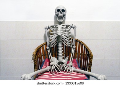 Fake human skeleton sitting on a chair in white room.