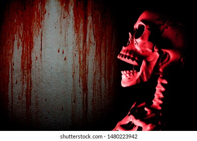 Fake human skull head and dark gloomy wall with red blood stain background, halloween concept.