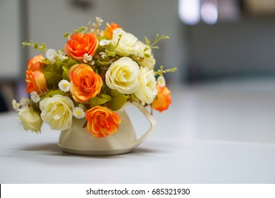 Fake or mock up bouquet flowers in a vase on the table in meeting room. copy space for text