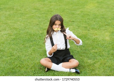 Fake mustache. Little child point at prop mustache. Party look of funny child. Small child sit on green grass. Cute child in school fashion style. School farewell party. Childhood fun. Mustache mania.