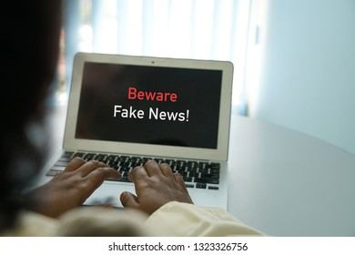Fake news concept - female hands on laptop with words beware fake news appear on screen