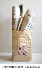 "Fake news concept - word ""Fake News"" on paper bag filled with newspapers"