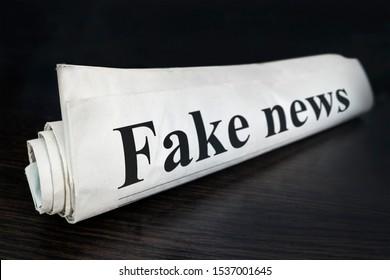 Fake News Newspaper on desk in the office. Daily news newspaper headline reading fake news concept for false event news headline. Rolled Up Newspaper. concept of false. deceit, falsehood
