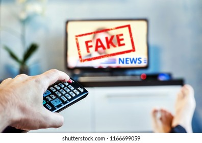 Fake News Propaganda HOAX Political TV Internet Social. young man watching the fake news report on TV at home. Agitation and propaganda in the modern television. switching channel on remote control
