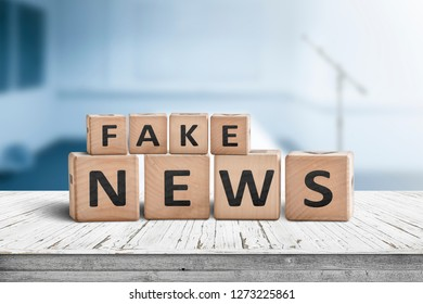 Fake news sign on a wooden desk in a blue room with a blurry background