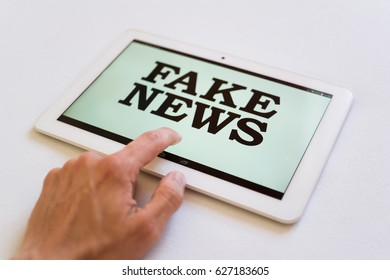 Fake News - user of digital device reads false information hoax, disinformation, propaganda. Misleading and brainwashing of reader (very low depth of field)