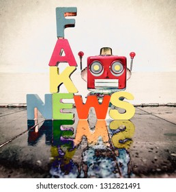 FAKE NEWS with wooden letters on an old wooden floor wit retro toy robot head