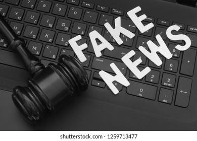 Fake news words and gavel on computer keyboard