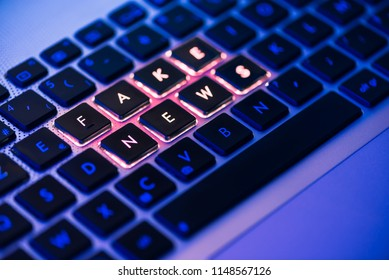 Fake news written in red on a backlit laptop keyboard close-up with selective focus in a blue ambiant light