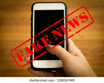 Fake news with young female hand holding smarhphone and wooden background. Conceptual image for social network.
