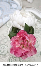 Fake pink and white peonies in white vase on table