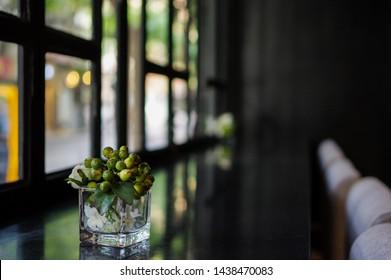 Fake plastic flower green little pomegranate on black table near window