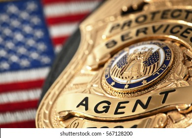 Fake prop badge with American flag in the background. Shallow depth of field with focus on the word agent.