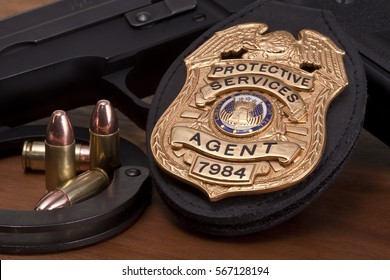 Fake prop badge with bullets, handgun and handcuffs on wood background.Law enforcement and security.