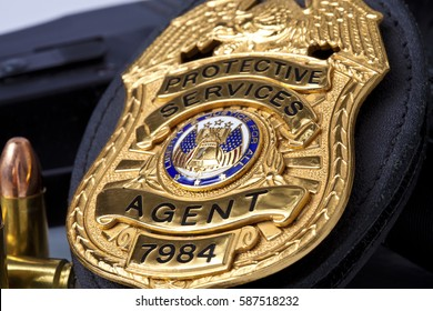 Fake prop badge designed by photographer on wood with firearm and bullets. Badge number is also fake.  Macro shot with focus on the word agent.