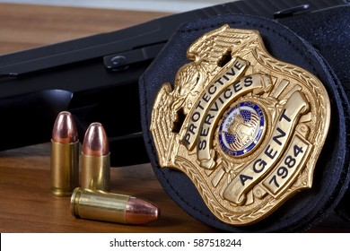 Fake prop badge designed by photographer on wood with firearm and bullets. Badge number is also fake.  Macro shot with focus on the word agent..