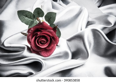Fake red roses on silver satin