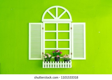 Fake white window decorated with pots of flowers on bright green wall background, concept of creative interior/exterior or home decoration