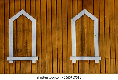 Fake window frames on a yellowish wall  in late afternoon sunshine