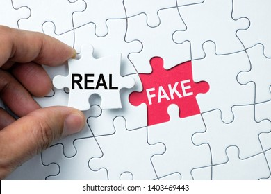 Fake word on missing puzzle with a hand hold a piece of real word puzzle