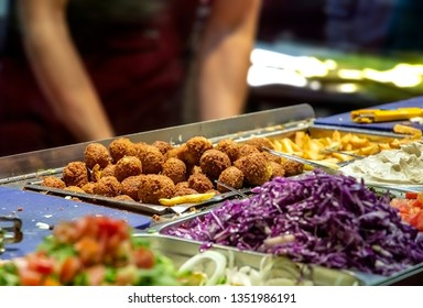 Falafel balls and chopped vegetables on a store desk