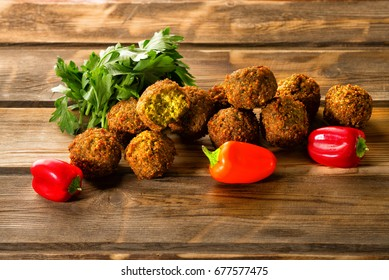 Falafel balls and green fresh parsley and mini sweet pepper on a wooden background. Falafel is a traditional Middle Eastern food, commonly served in a pita.