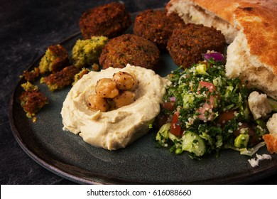 Falafel balls with hummus, tabouleh salad and pita. Close up.