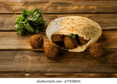 Falafel balls in a pita and green fresh parsley on a wooden background.Falafel plays an iconic role in Israeli cuisine and is widely considered to be the national dish of the country.