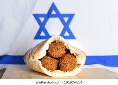 Falafel balls in a pita on wooden table over Israel flag background. Falafel plays an iconic role in Israeli cuisine and is widely considered to be the national dish of the country.Copy space for text