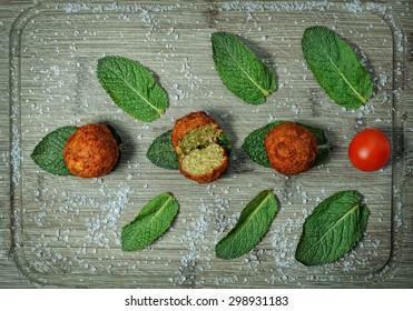 Falafel balls served on a wooden board with fresh mint leaves
