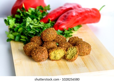 Falafel balls,sweet red pepper and green fresh parsley on a wooden background.Falafel is a traditional Middle Eastern food.