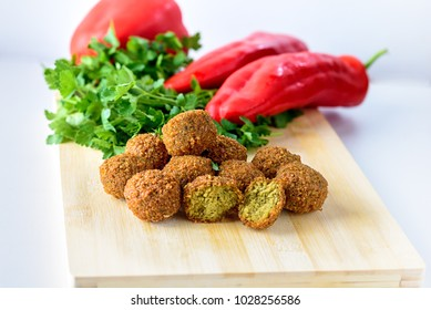 Falafel balls,sweet red pepper and green fresh parsley on a wooden background.Falafel plays an iconic role in Israeli cuisine and is widely considered to be the national dish of the country.