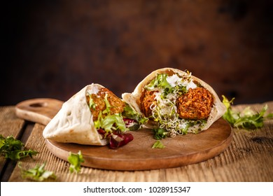 Falafel and fresh lettuce in pita bread on wooden table