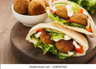 Falafel and fresh vegetables in pita bread on wooden board.