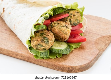 Falafel and fresh vegetables rolled in pita bread on wooden board