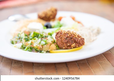 falafel (fried ball with chickpeas or fava beans) in white dish with mezze or meze, selection of typical Arabic appetizers (hummus, baba ghanoush, Feta cheese, Marrakesh salad, tabule, olives)