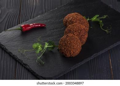 Falafel with garlic sauce on a black stone tray. Vegan food