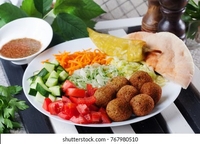 falafel plate on top to garnish, carrot, cabbage, onion, cucumbers, tomatoes, still life, dish