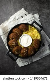 Falafel with rice and sauce in iron pot
