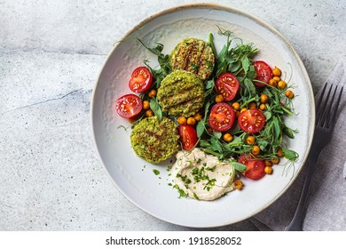 Falafel salad with tomatoes, hummus  and pea sprouts in a gray bowl. Plant based food concept.