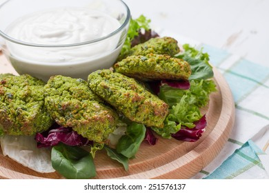 Falafel served with tahina sauce on wood board, white wood background, closeup