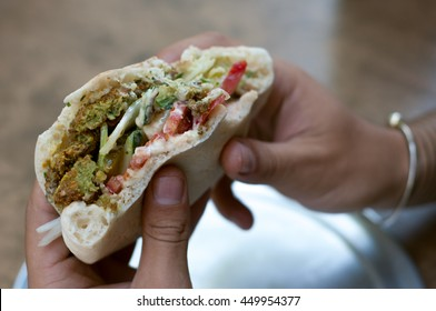 Falafel with tahini sau?e and fresh vegetables in pita bread on wooden table. Delicious israeli snack ready to eat. Man eating falafel