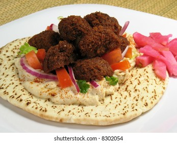 Falafels served on pita bread with hummus, lettuce, tomato, red onions, and a side of turnips pickled in beet roots.