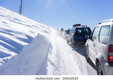 FALAKRO, GREECE - FEBRUARY 11, 2013: Visitors waiting near their cars for the Snowmobile to remove the snow from the road in Falakro, Greece. Falakro Mountain is located in the area of Dramas.